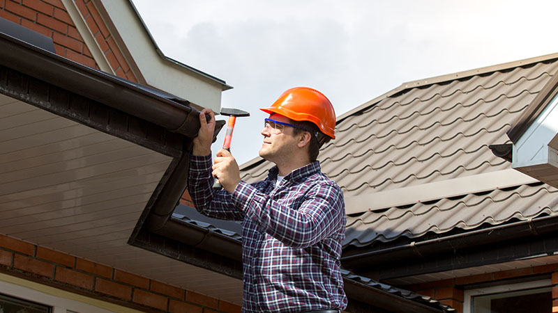Man with orange hard hat inspecting roof
